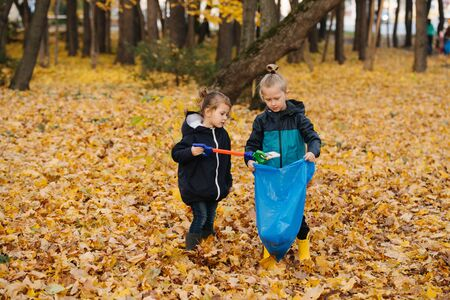 Little kid siblings collecting trash in a seasonal forest at autumn with a group of volunteers. Girl uses plastic robot arm as a littler picker and then bringing it to the boy holding the bag.