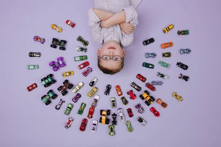 Happy little ginger boy lying on the floor surrounded by toy model cars all around him. They placed in half-circular shape in several rows. He holding hands crossed, taking pride in amounts. Over pink