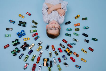 Happy little ginger boy lying on the floor surrounded by toy model cars all around him. They placed in half-circular shape in several rows. He holding hands crossed, taking pride in amounts. Over blue 写真素材