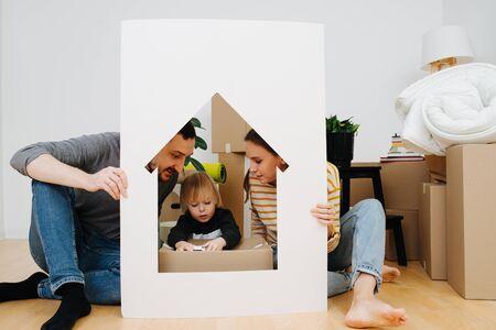 Netter kleiner Junge, der mit Spielzeugmodellauto in einem rahmenähnlichen Haus spielt, das von seinen Eltern gehalten wird. Mutter und Vater sehen ihn liebevoll an. Umzug in ein neues Wohnkonzept