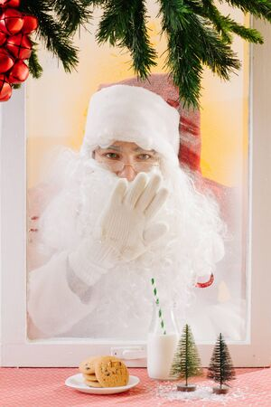 Santa looks at the camera through the window and wipes it from hoarfrost.