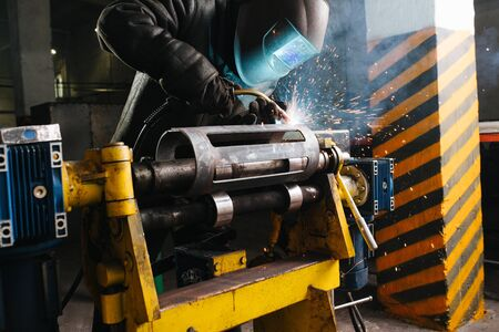 Working welder in protective mask and clothing. He's welding metal piece, fixed with industrial clamp. His mask glowing blue, sparks flying in the air. Workshop is big and resembles hangar. Standard-Bild