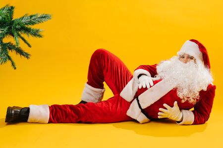 Santa Claus lying on the floor in impudent shameless manner. He lies provocatively on one side with knee bent, holding his arms on his huge belly. Looking straight at camera. Over yellow background.