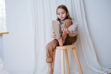 Attentive little girl in a beige knitted sweater sitting on a stool at home, in front of a curtain. She's puting sandals on her small bare feet. Top view.