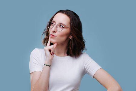 Schönes modernes Mädchen in nachdenklicher Pose in einem weißen T-Shirt, das den Finger ans Kinn legt, sich dreht und nach rechts schaut Standard-Bild