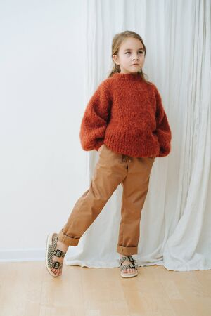 Little girl in dark orange knitted sweater, brown jeans and leopard sandals. She's posing for photo, trying to look cute and fashionable. One leg on toes. Full length.