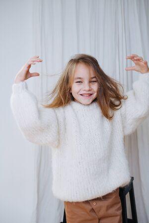 Lächelndes, ironisches, süßes kleines Mädchen mit einfach angezogenem weißen, flauschigen Strickpullover. Sie drückte ihren Kopf aus dem Kragen, und er ist total durcheinander und elektrisiert ihre Haare. Halbe Länge. Zu Hause.