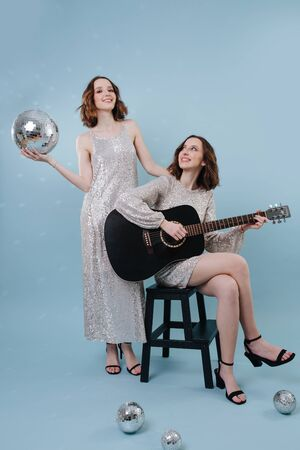 Two twin sisters at a party holding a disco ball and a guitar in their hands