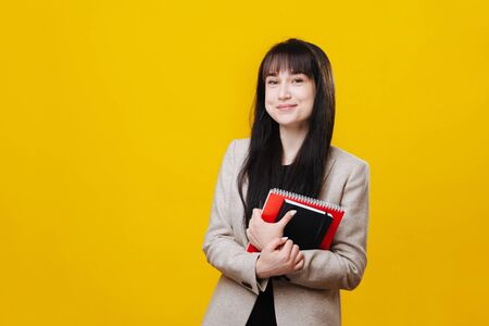 Cute charming young business woman with perky smile over yellow. She has long dark hair, wearing gray jacket, holding pair of notebooks with both hands.