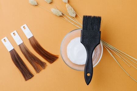 Composition of locks of dyed hair samples next to a bowl of die developer with brush across and couple of fluffy cereal ears. Over orange surface. Top view. Arranged in straight and diagonal lines.