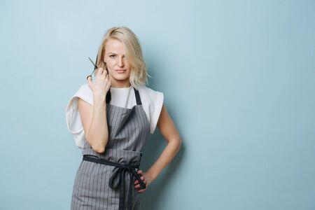 Mörderische wütende, verrückte blonde Friseurin in Schürze, die eine offene Schere neben ihrem Gesicht über blauem Hintergrund hält. Standard-Bild