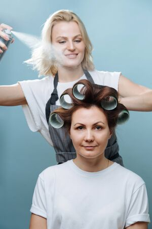 Smiling blonde female hairdresser in apron spraying client's brown hair on rollers over blue background. She's using setting spray, enthusiastic about her work.