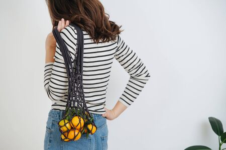 Brunette woman turned her back, posing with a net bag containing about a kilo of mandarins. Shes dressed casually, wearing jeans ond striped shirt. From behind. Over white. 版權商用圖片