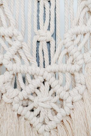 Whitish macrame tapestry up close. Knots, ropes and tassels arranged in a pattern as a form of art. It has a rectangular shape in the middle and triangles connected to it.