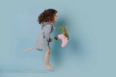 The curly girl plays with stick horse.