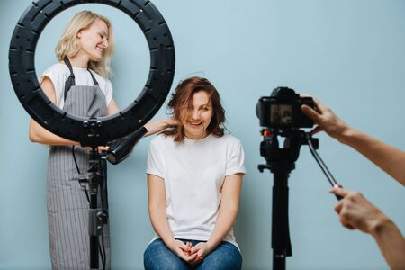 Blonde female hairdresser behind ring lamp in apron drying client's brown hair over blue background. She's using a hair blow dryer. Her happy customer giggling in the chair, while photo being taken.