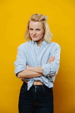 Portrait of an attractive blonde woman with a perky smile in a in a belly-tied jeans shirt with her arms crossed over yellow background. She's posing for a photo. With elaborate hair set. Half length.