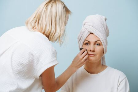 Focused blonde female hairdresser in apron is applying setting powder on client's cheeks, while her hair bleaching. Over blue background. Client is peaceful and tranquil, looking nowhere.