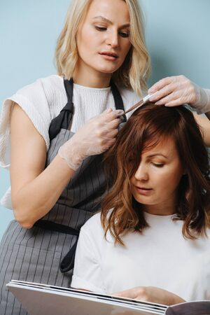 Blonde female hairdresser in apron selecting hair tone over blue background. She's calculating in her head how to mix developer to have this end result. All the while customer flipping catalog pages. Banque d'images