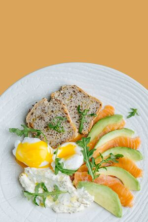 Light meal. Poached eggs, bread with salmon and avocado slices served on a white plate with some greens. Top view. Over orange background.