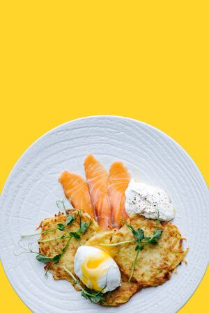 Fried potato pancakes with poached egg, salted salmon, sour cream and some greens on a white plate over yellow background.