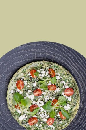 Peppered omelet with greens, spinach, tomatoes and cheese on a textured plate over green background. Top view. It has round circular form.