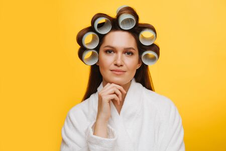 Portrait of a woman sitting with hair in rollers supporting chin with fingers Stockfoto