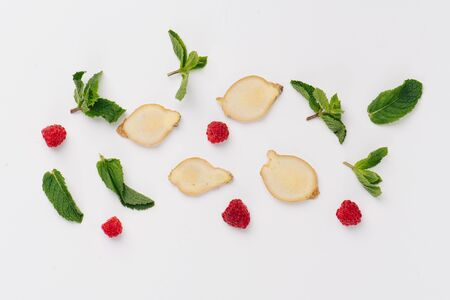 Flat lay of nice pieces of mint leaves, raspberries and ginger root slices placed on a white surface in a pattern, making a texture. Top view