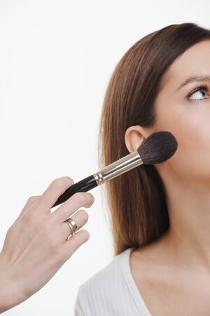 Close up image of a hand applying setting powder to a woman's face. Creating great texture. Brunette, in a u-neck shirt. Cropped, half face.