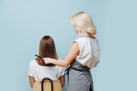 Smiling blonde female hairdresser in apron combing client's straight glistening brown hair over blue background. From behind the back.