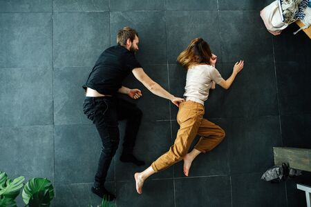 Man and woman depict running while lying on the floor. He's chasing her, grabbing her by the belt.