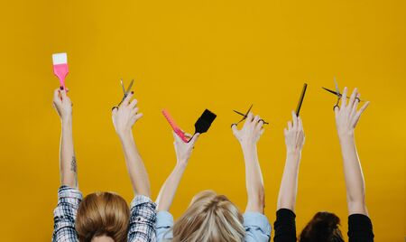 Women with their hands in the air holding hairdresser tools, such as brushes, scissors and combs over yellow background. From behind. Cropped. No bodies.