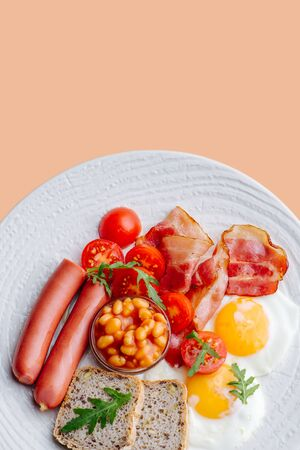 Hearty breakfast: fried eggs, bread, sausages, bacon, cherry tomatoes and beans on a white plate over peach background 写真素材
