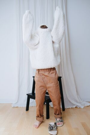 Funny little girl struggling to put on white fluffy knitted sweater. It does not slide down on inself, so her head and arms still inside. At home, in front of a curtain. Full length. Standard-Bild