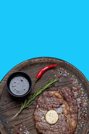 Grilled juicy steak on a wooden plate over blue background. Along with chili pepper, cheese, sauce, salt, berries and savory thyme stem scattered across a plate. Top view