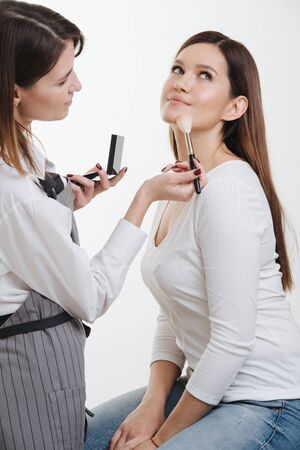 Stylist woman is applying setting powder onto clients face in a bright room