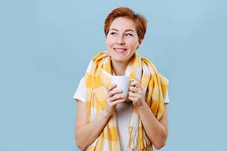 Portrait of a happy middle aged woman with short ginger hair wearing big yellow scarf holding mug with hot drink. Fight against a common cold. Over blue background.