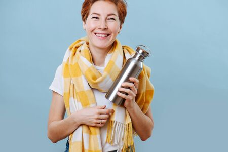 Portrait of a cheerful middle aged woman with short ginger hair wearing big yellow scarf holding vacuum bottle with hot drink. Fight against a common cold. Over blue background. Stock Photo