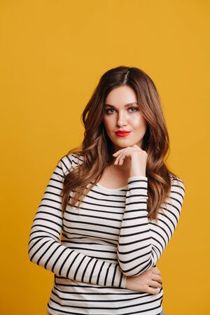 Confident middle aged brunette with vibrant red lipstick in a striped black and white shirt and ring earings over yellow background. Leaning chin on her fingers