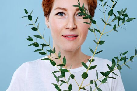 Close up portrait of a happy middle aged woman with short ginger hair holding eucalyptus branch. She's wearing casual clothes, white T-shirt. Over blue background.