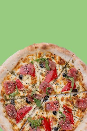 Sliced, freshly made pizza with ham, tomatoes, olives and greens over green background. Top view