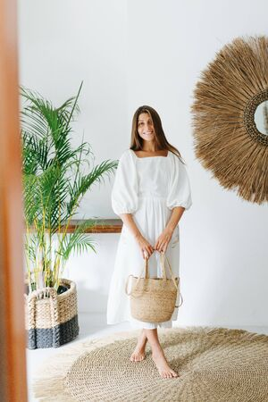 Happy modest young woman in a light white summer dress posing for a photo in a tropical style room. She's standing legs-crossed, holding wicker handbag with both hands.