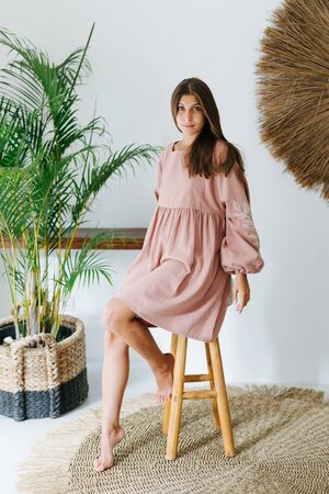 Pretty emotionless young woman in a pink dress posing for a photo in a tropical style room. She elegantly sits on a high stool.