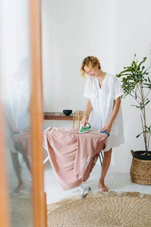 Barefoot cheerful young woman with short dyed blond hair and in a white dress shirt ironing clothes on a board at home