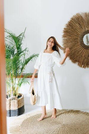 Happy young woman in a light white summer dress posing for a photo in a tropical style room. She's holding wicker handbag in one hand, pulling lock of hair with the other.