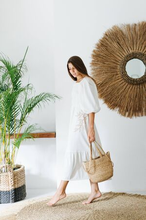 Happy young woman with inocent look in a light white summer dress posing in a tropical style room. She's holding wicker handbag in one hand, graciously stepping on the floor with her foot. Stock Photo