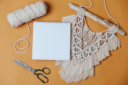 A blank sheet of notepad for your text, lying on the table with macrame embroidery, scissors and rope