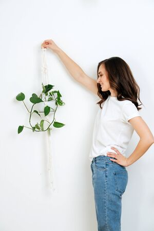 A pretty woman hold a pot of macrame with beautiful plant. She's wearing a white T-shirt and jeans, against a white wall Stock fotó