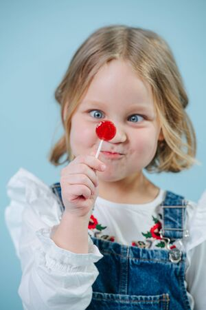 Funny little blonde girl in jeans overalls looking at lollipop candy holding it close to her face so her eyes are lazy, inflating cheeks. Hence the funny face. Over blue background.