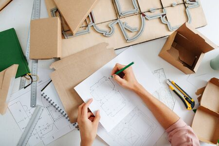 Designer in the works, she makes a drawing of a new box. A view from above on the hands of a woman with a pencil and a drawing on the background of the desktop with accessories and shtantsform